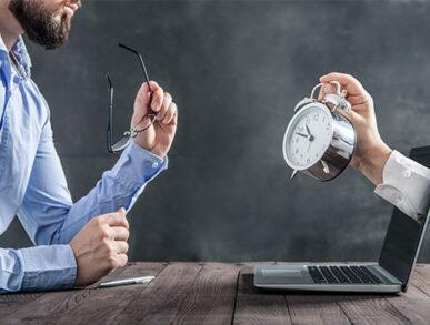 Mann mit Brille vor Computer, sieht auf tickende Uhr